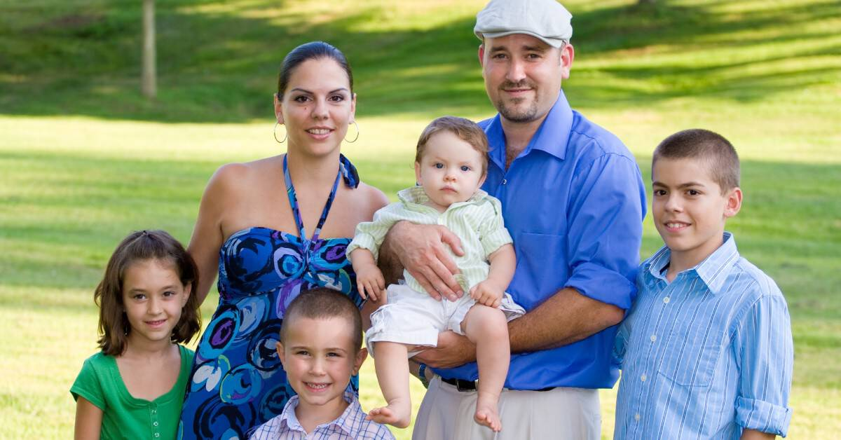 Image of a family standing for their picture all facing and smiling at the camera.