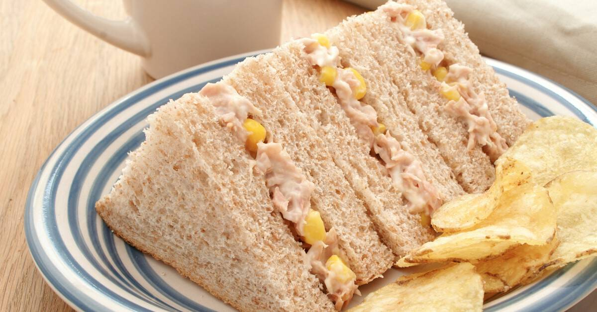 Image of tuna sandwiches on wheat bread without the crusts on a plate with potato chips on the side.