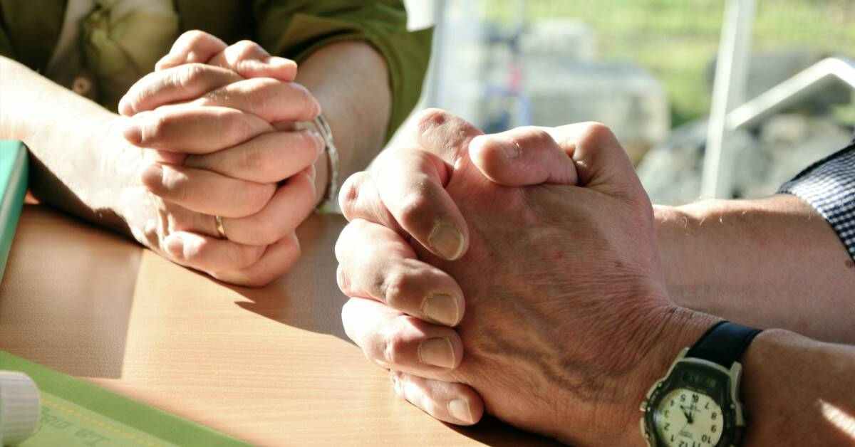 Image of a hands of a couple who are sitting together. Each of their hands clasped independently.