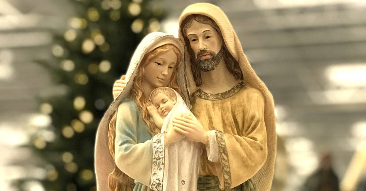 Image of a statue of the Holy Family: the infant Jesus held by Mary, and Joseph.