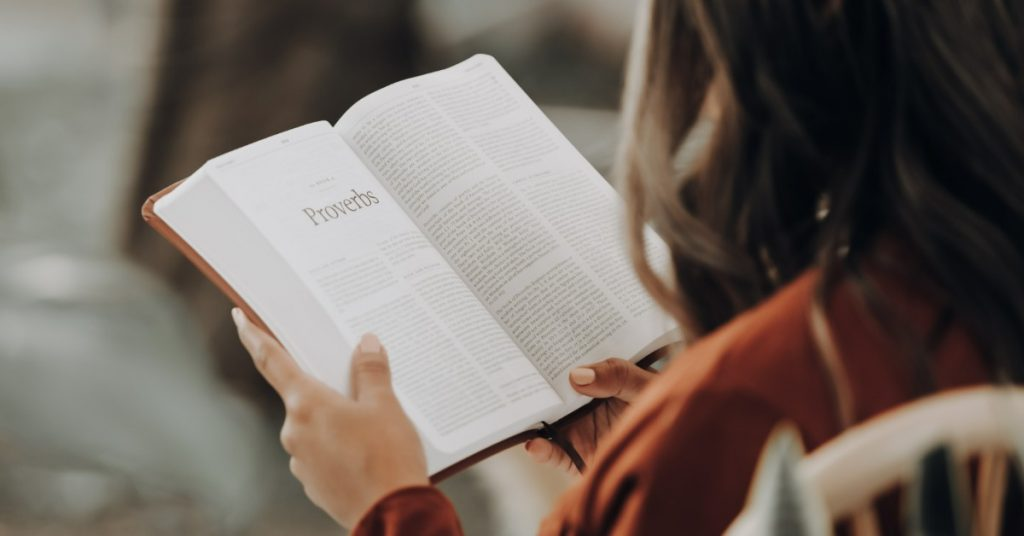 Image of a woman reading her Bible. It is open to the Psalms.