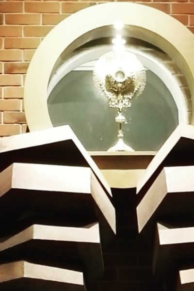 Image of a church with a monstrance below it. The monstrance is huge: two hands holding a circle that has the monstrance inside of it containing the Blessed Sacrament.