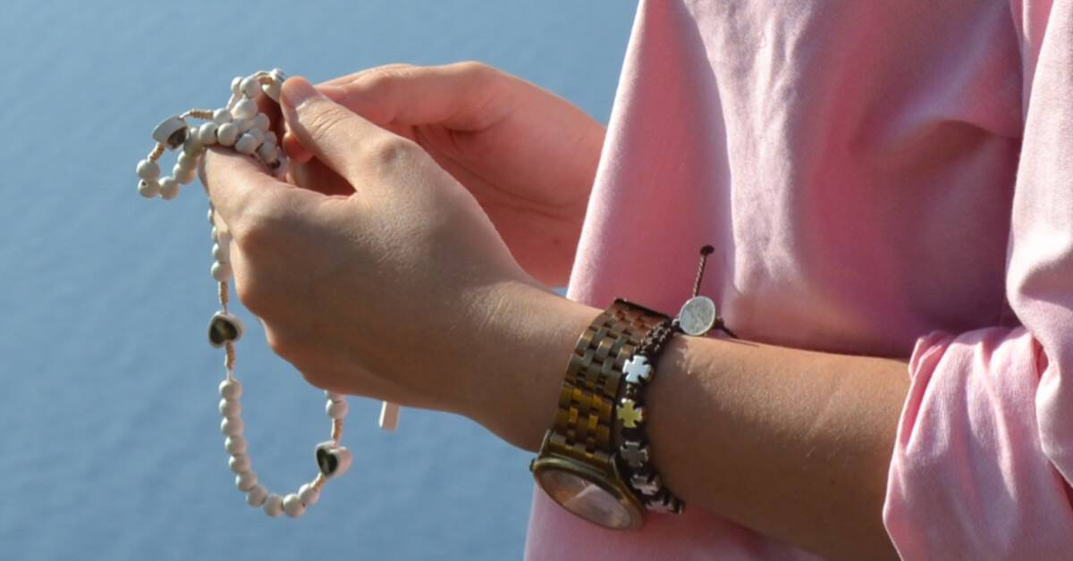 Image closeup of a the hands of a woman wearing pink holding the Rosary to pray.