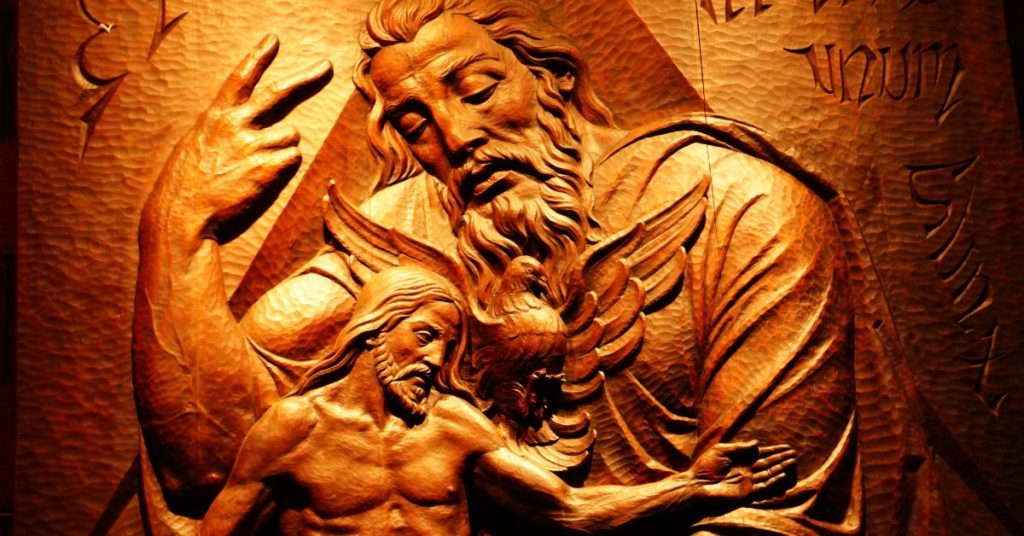 Image of a carving of the Blessed Trinity. God the Father is personified, Jesus is risen, and the Holy Spirit is in the form of a dove.