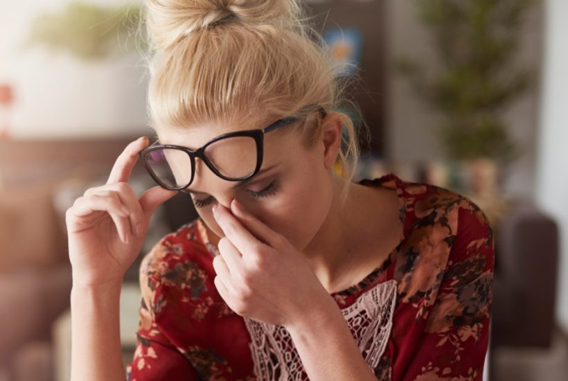 Image of a woman sitting holding her glasses up with one hand and pinching the bridge of her nose with her other hand in a gesture of frustration.
