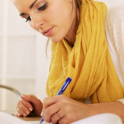 Image of a woman sitting at a desk writing something on a piece of paper.