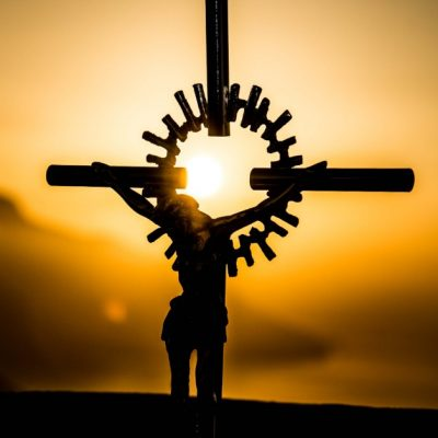 Image of Jesus crucified with a golden sunset in the background.