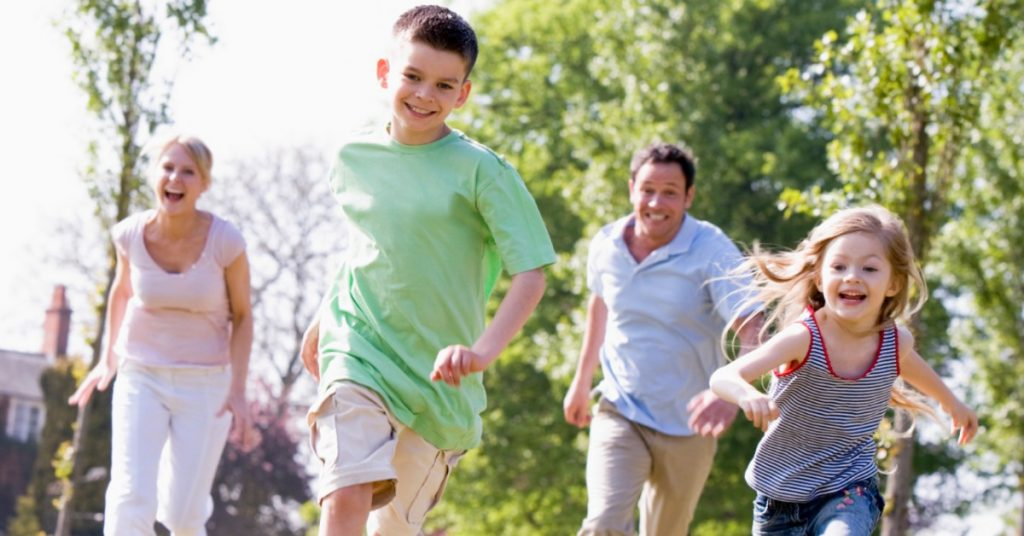 Image of a family-Mom, son, Dad, and daughter-running outside on the grass.