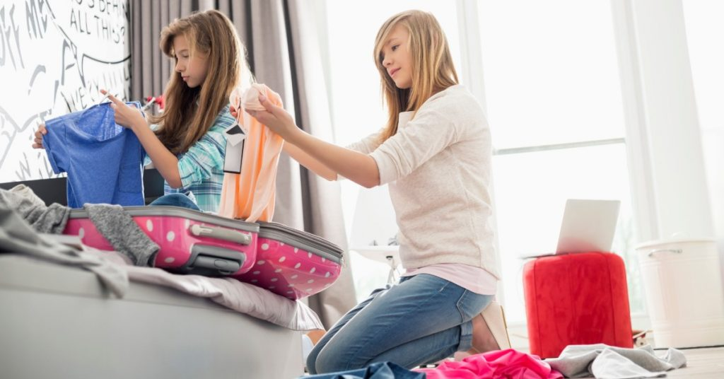 Girls folding laundry in their bedroom.