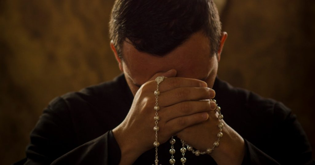 Image of a priest, head in his hands, holding and praying a Rosary.