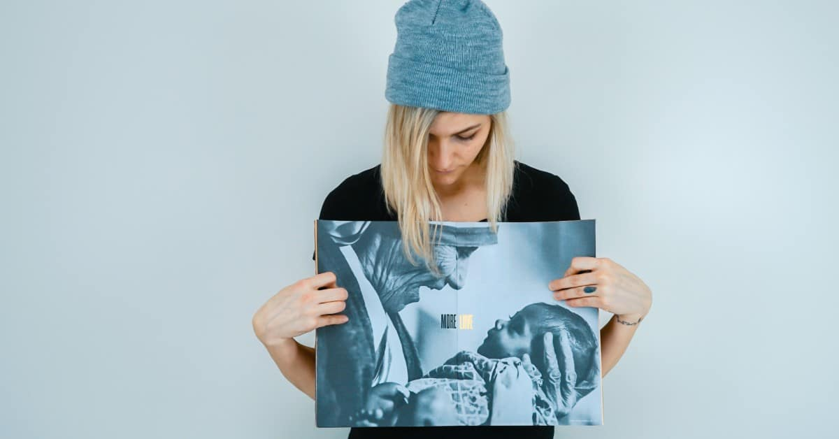 Image of a young woman wearing a blue knitted cap holding up to the camera a large photo of St. Mother Teresa holding a baby and looking into his eyes and smiling.