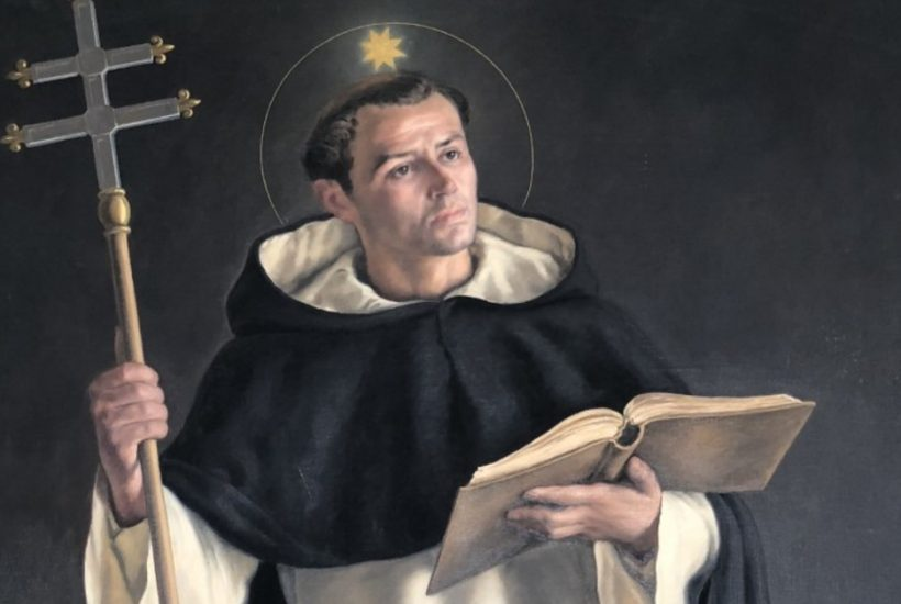Image of Saint Thomas Aquinas wearing a religious habit and holding a cross in one hand and an open book in the other. There is a ball of light above and a halo around his head.