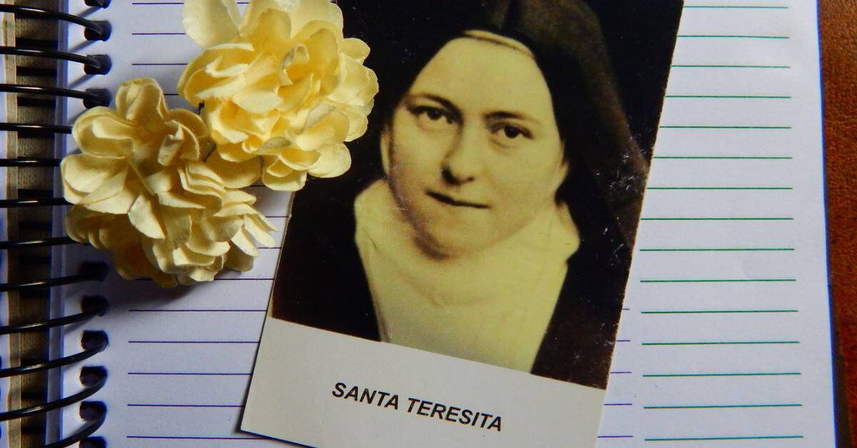 Image of a photo of St. Therese on a lined paper spiral notebook with a yellow flower.