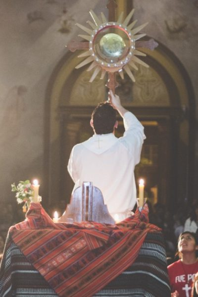 Image of a priest holding a monstrance high while people crowd around him in adoration of the Blessed Sacrament.