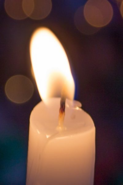 Image of a lit, single white candle.