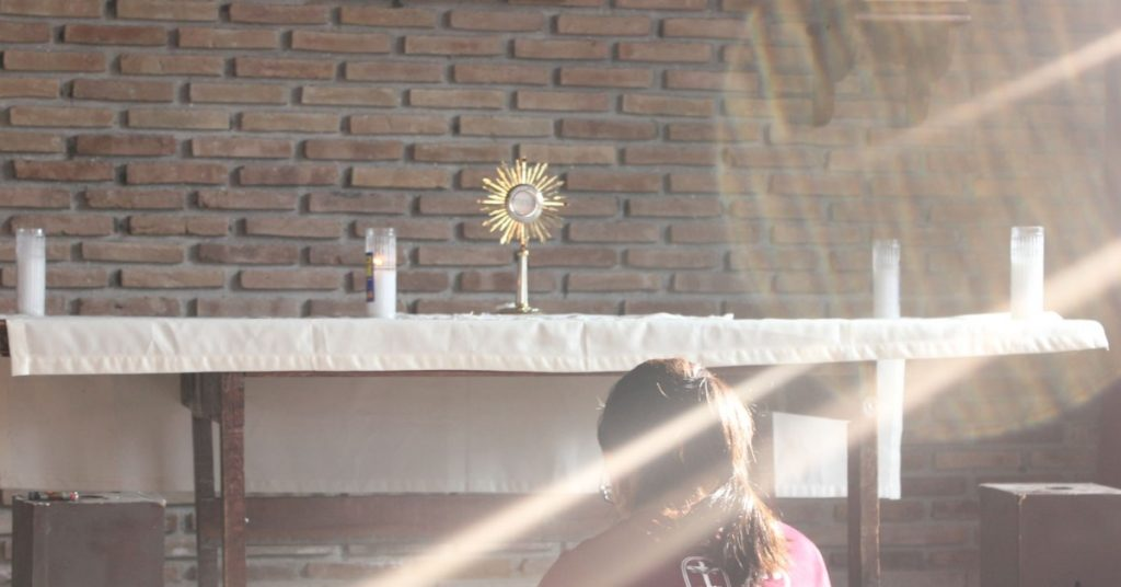 Image of a woman kneeling in prayer in church in front of an altar where the Blessed Sacrament is exposed in a monstrance..