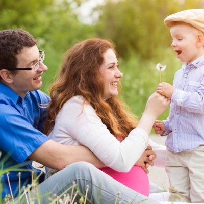 Image of a man and his pregnant wife sitting together outside while their happy little son brings them a dandelion flower.