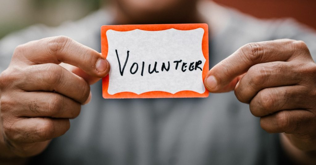 Image of the hands of a man holding a name tag with the word volunteer on it towards the camera.