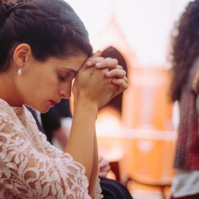 Image of a woman kneeling in prayer in church.