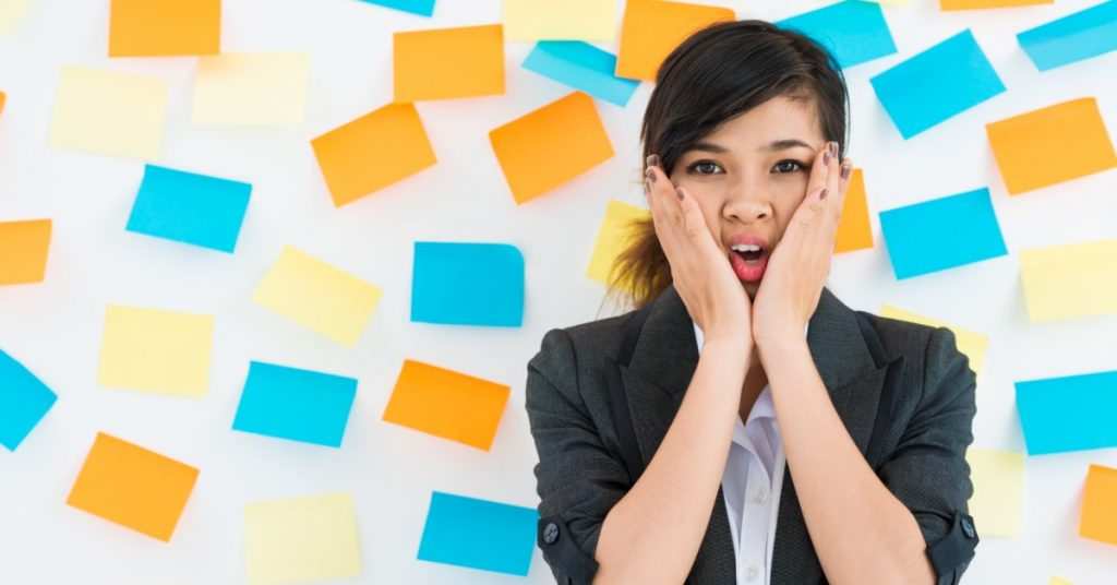 Image of a woman with her hands on either side of her face looking stressed out with post-it notes of different colors covering the wall behind her.