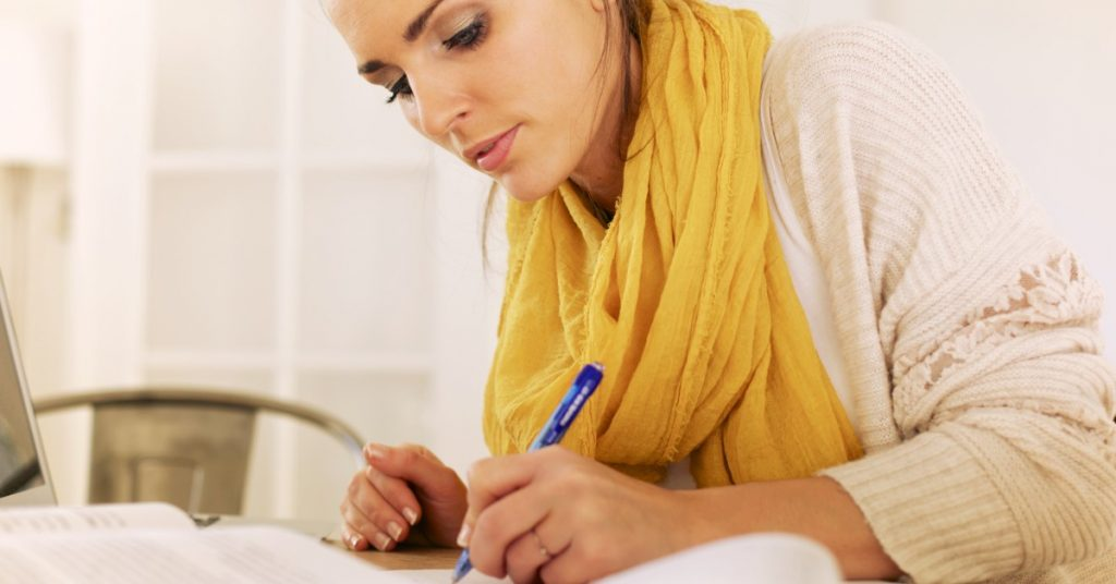 Image of a young woman writing in a notebook.