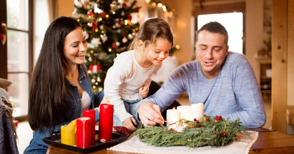 Image of a couple with their daughter at a table with a wreath and candles with a Christmas tree in the background.