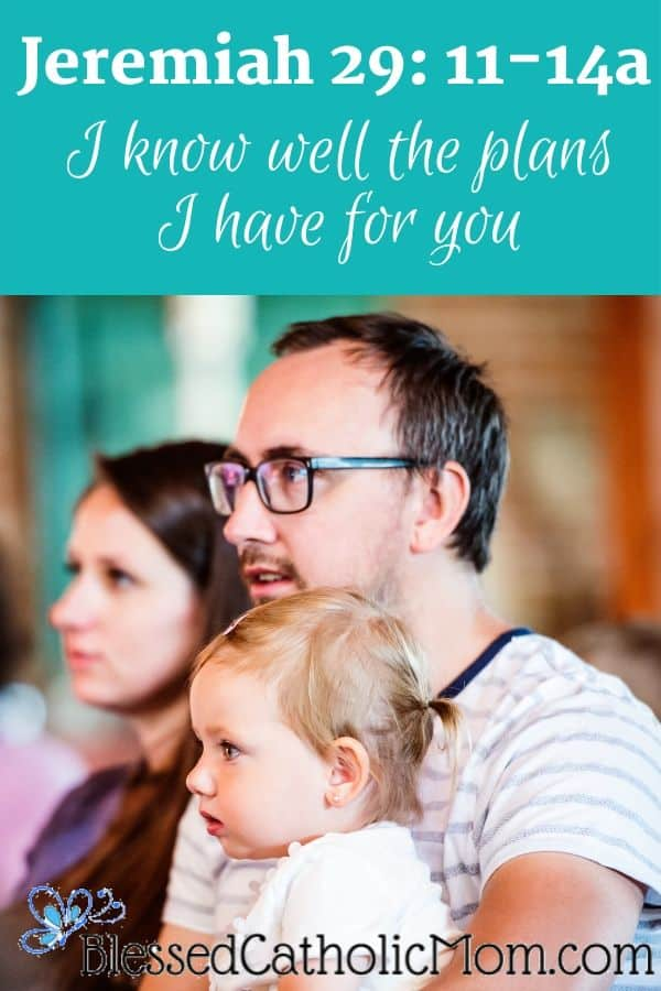 Image of a Dad holding his daughter sitting beside his wife at church together.