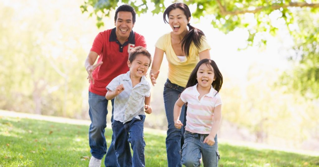 Image of a Dad, Mom, son, and daughter running together outside having fun.
