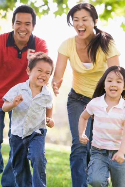 Image of a dad, mom, son, and daughter running outside together, laughing and smiling.