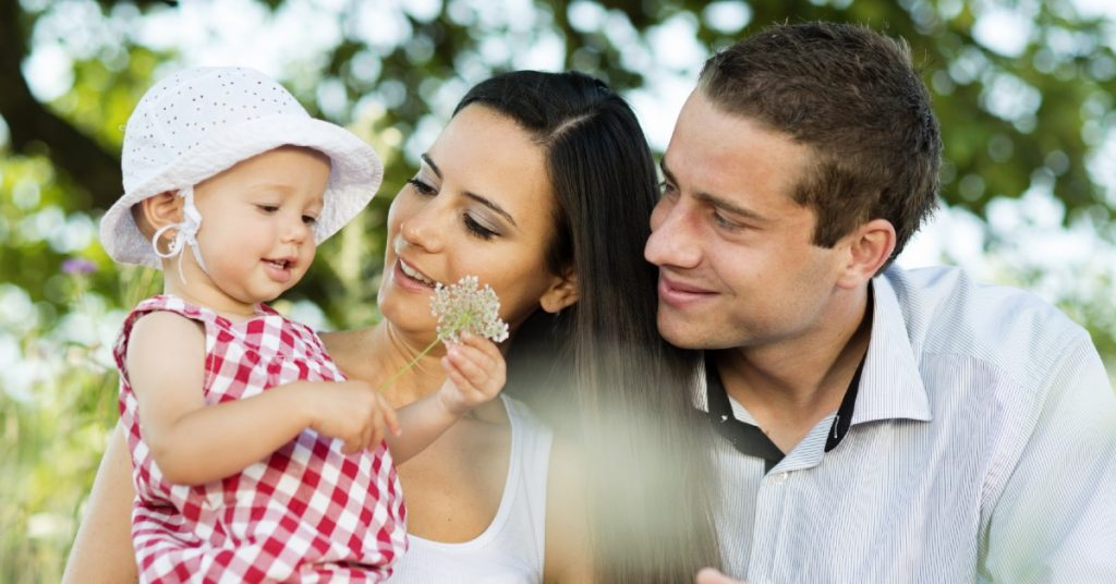 Image of a Mom and Dad sitting outside holding their young daughter who is holding a flower in her hands.