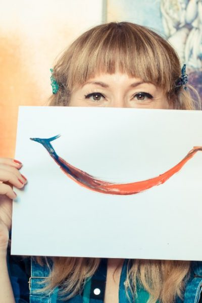Image of a woman holding a paper in front of the lower half of her face that has a smile painted on it. She is holding a paint brush in one hand.