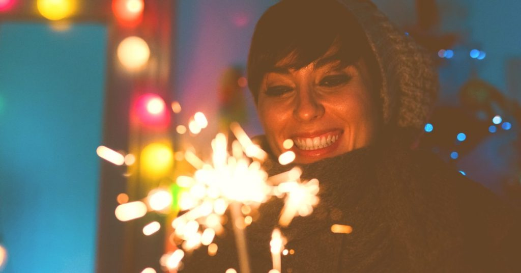 Image of a smiling woman all bundled up for the cold weather standing outside holding a lit sparkler.