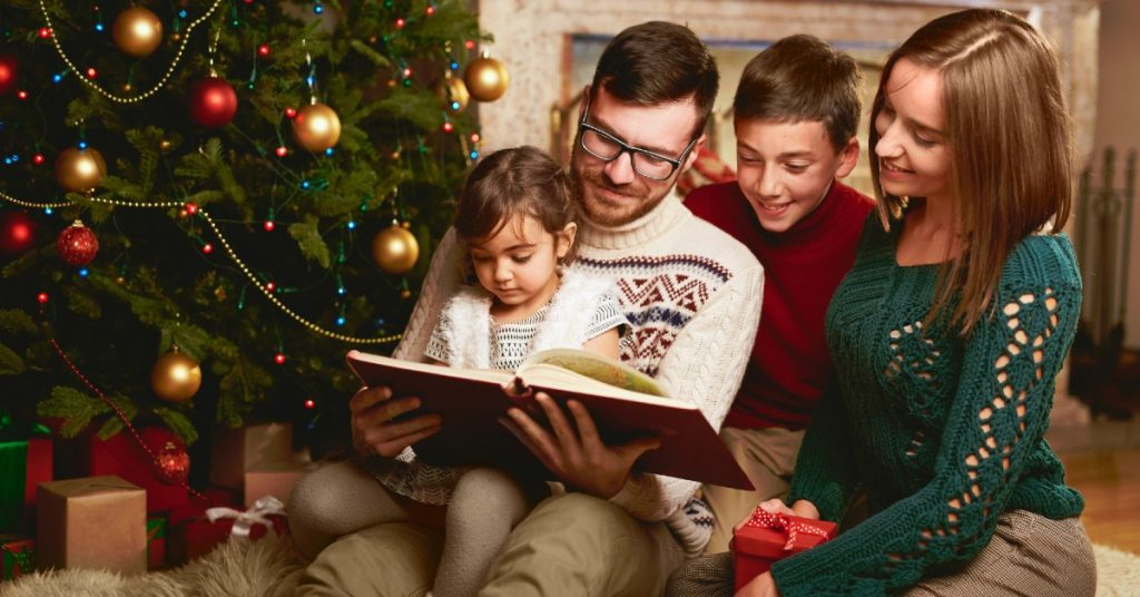Image of a smiling family of a Dad, Mom, son, and daughter sitting on the floor reading together next to their Christmas tree.