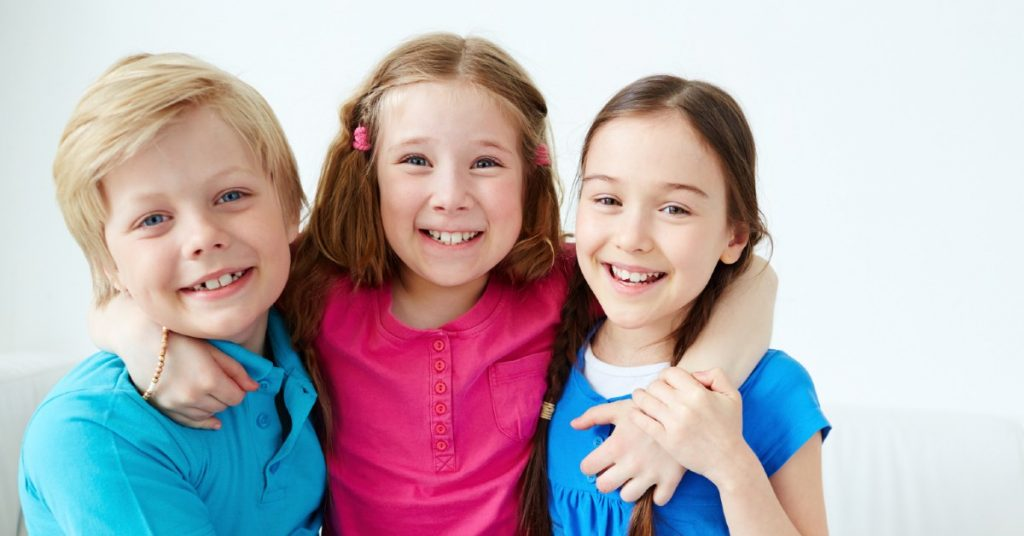 Image of a boy and two girls with their arms around themselves and smiling at the camera.