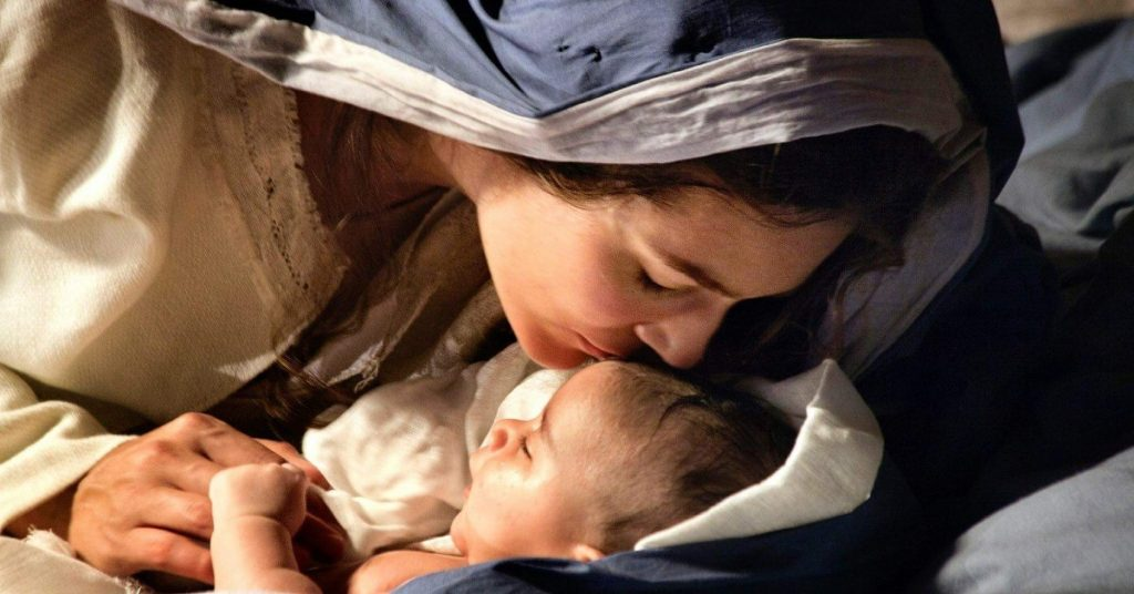 Image of Mary leaning over baby Jesus and giving Him a kiss on His forehead.