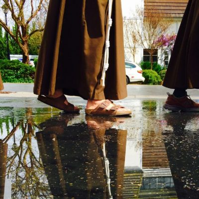 Partial image of three Franciscan men walking through a puddle of water with their reflections showing in the water beside them.
