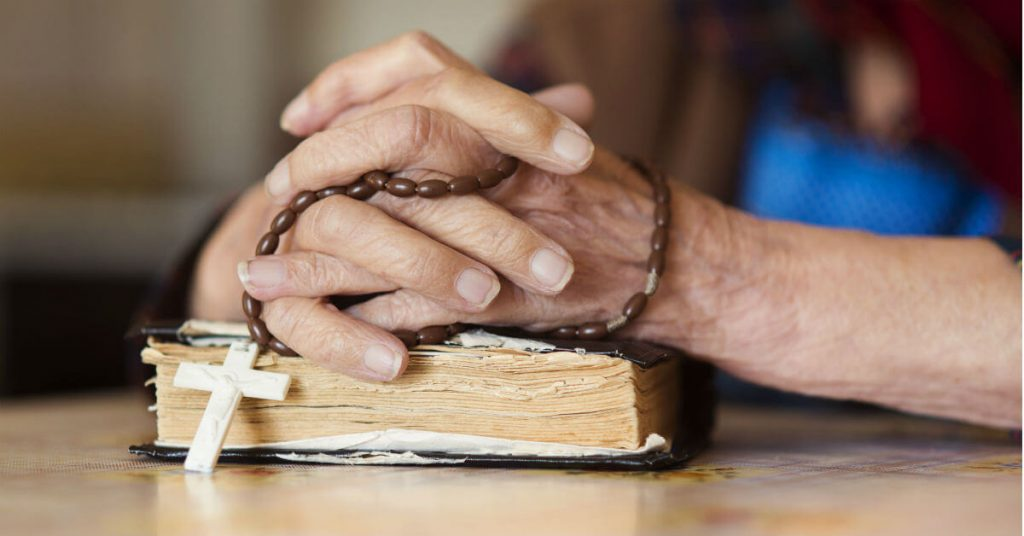 Image of two hands holding a Rosary, clasped together on top of a Bible.