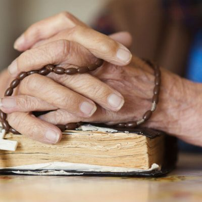 Image of two hands holding a Rosary that are clasped together on top of a Bible.