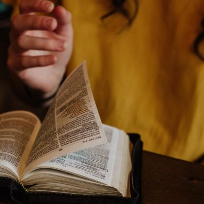 Image of a woman sitting at a table turning a page in the Bible that is open on the table in front of her.