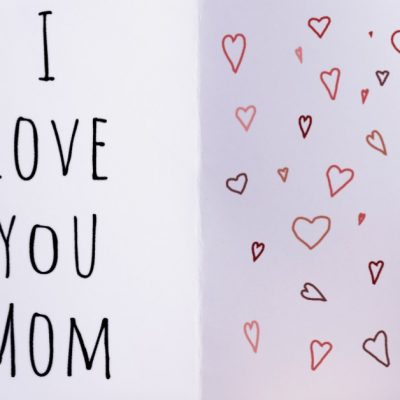 "Image of a woman's hands holding a cup of coffee in her left hand and an open card in her right. the card reads ""I love you Mom"" on the left side and has hearts drawn on the right side."