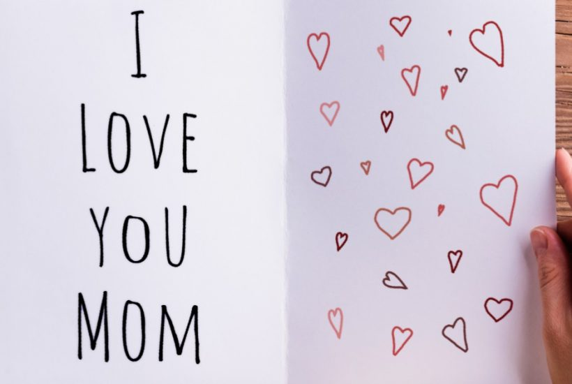 """Image of a woman's hands holding a cup of coffee in her left hand and an open card in her right. the card reads """"I love you Mom"""" on the left side and has hearts drawn on the right side."""