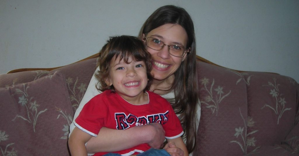 Image of a woman sitting on a rose colored couch holding her son as they are both looking and smiling at the camera.