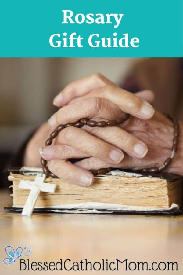 Image of two hands holding a Rosary, clasped together on top of a Bible. The text on the top of the image reads Rosary Gift Guide. At  the bottom of the image is a butterfly logo with the text Blessedcatholicmom.com.