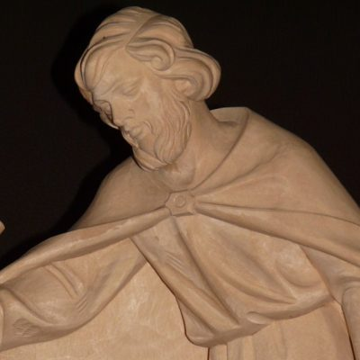 Image of a statue of St. Joseph, foster father of Jesus and protector of the Holy Family, wearing a traveling cloak and holding a staff in his right hand.
