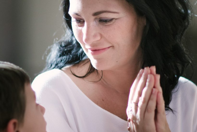 Image of a woman smiling while looking at her son while her hands are closed in prayer as she is holding her Rosary.