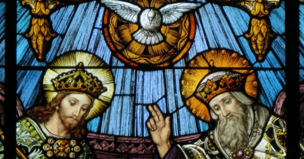 Image of a stained glass window of the Blessed Trinity: Jesus crowned on the left, the Holy Spirit as a dove in the center, and God the Father with His hand raised in blessing on the right side.