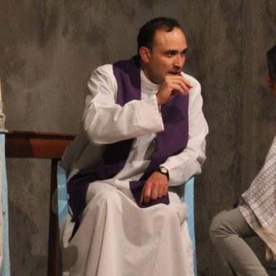 Image of a priest and a woman sitting down in Church, facing each other as the priest hears the woman's Confession.