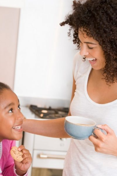 Image of a mom and her daughter in the kitchen with cookies and coffee, smiling at each other.