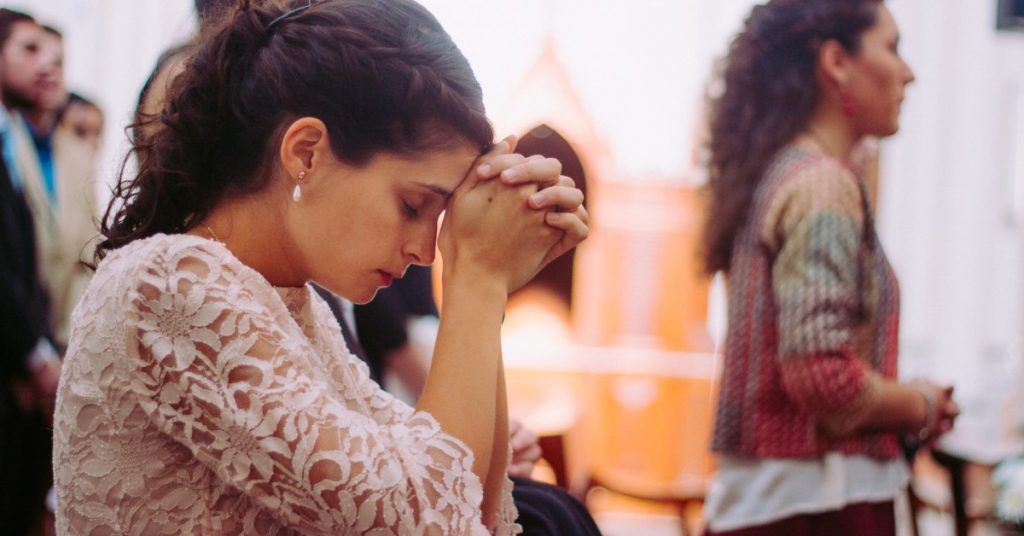 Image of a woman kneeling in a pew at church praying with her hands together against her forehead.