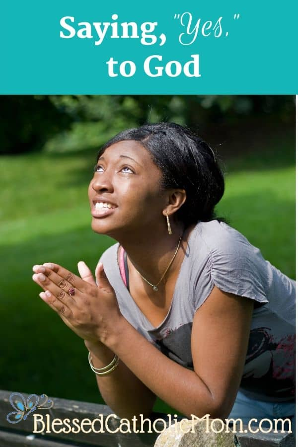 A young woman outside with her hands folded in prayer, looking up to the sky. The words across the top of the image read: Saying Yes to God.